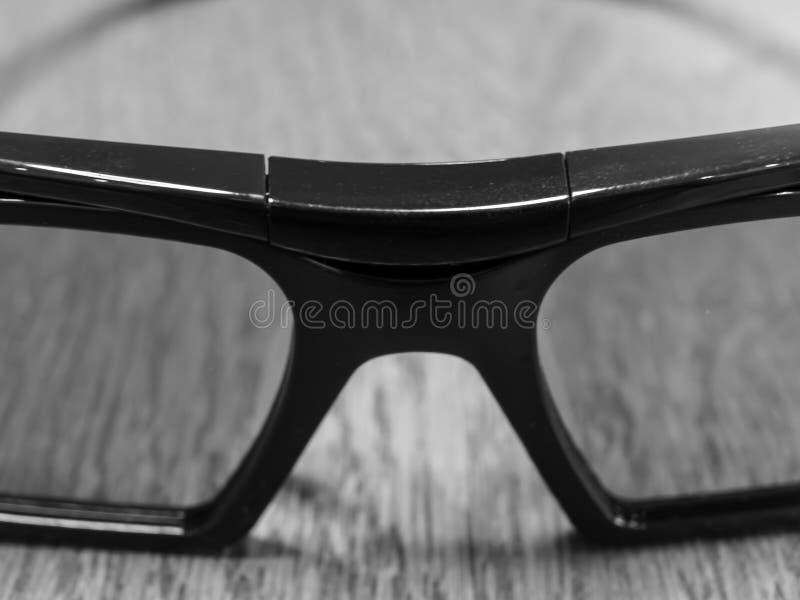 Donkere glazen die op een houten lijst liggen stock fotografie