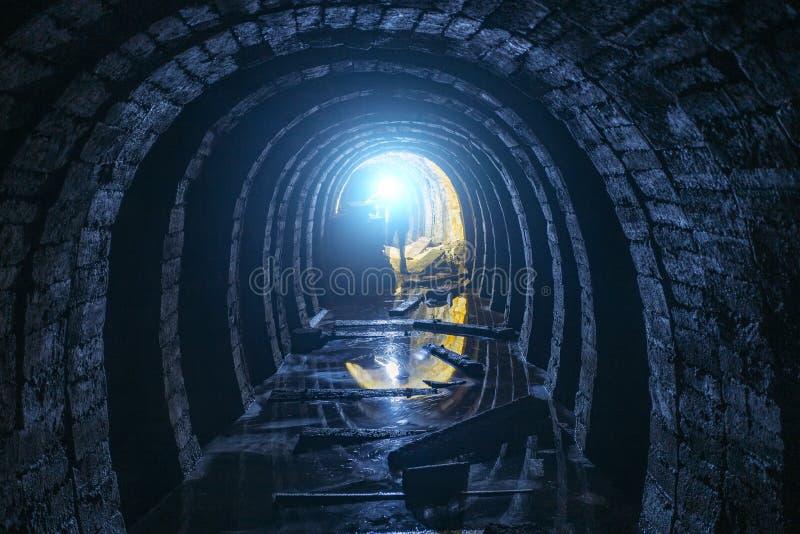 Donkere griezelige vuile overstroomde verlaten mijntunnel stock afbeelding