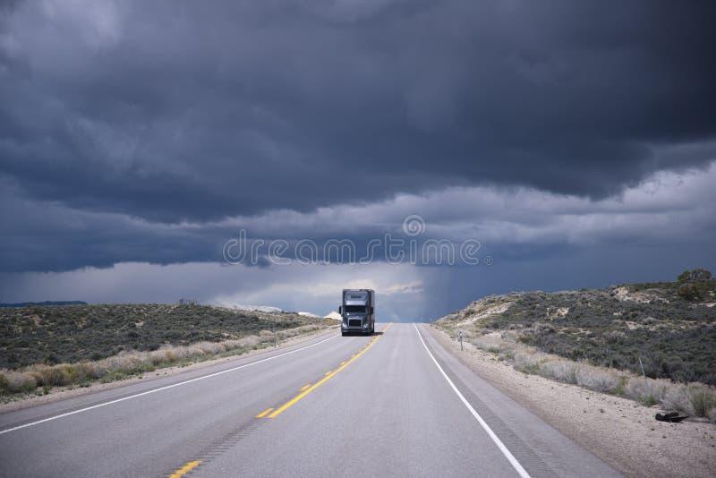 Donkere grijze semi-vrachtwagen op weg en stormende hemel stock foto's