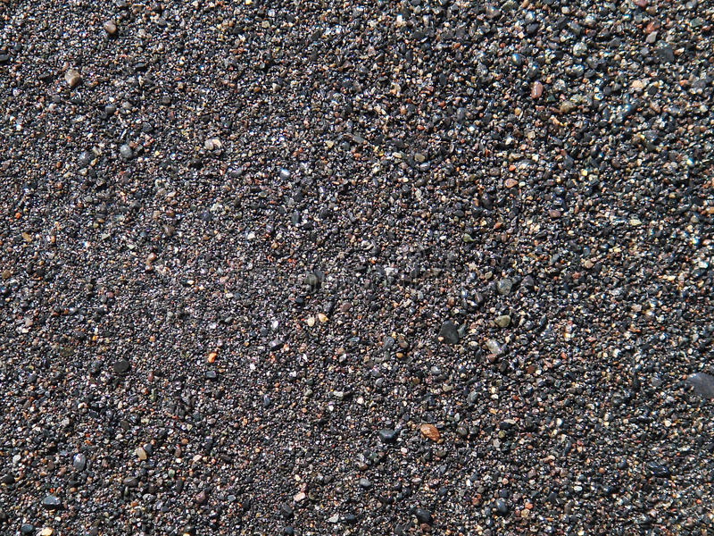 Donkere grijze zandoppervlakte, nat strand met vulkanische zandachtergrond royalty-vrije stock fotografie