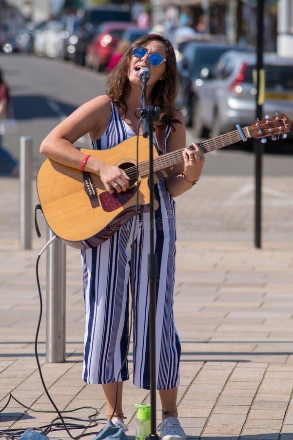 Donkere haired vrouwelijke zanger op straat met zonnebril en royalty-vrije stock fotografie