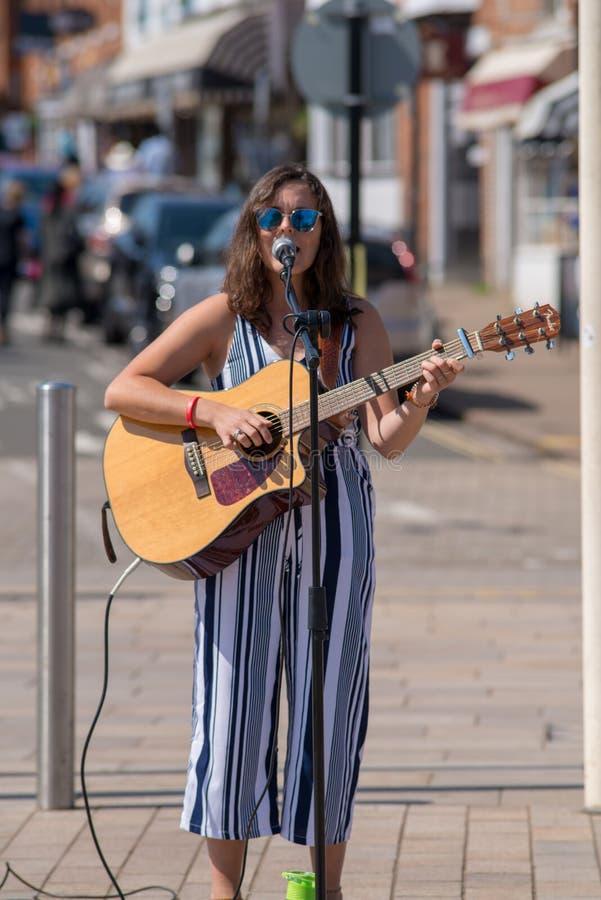 Donkere haired vrouwelijke zanger op straat met zonnebril en stock afbeelding