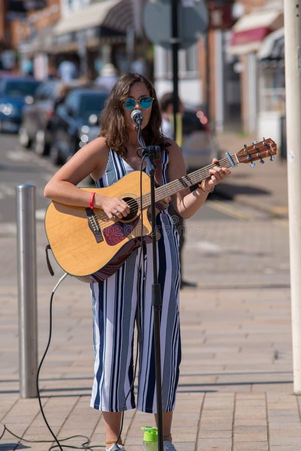Donkere haired vrouwelijke zanger op straat met zonnebril en stock fotografie