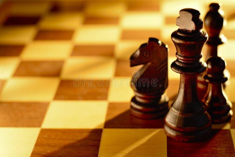 Donkere houten schaakstukken in een lichtstraal stock foto's