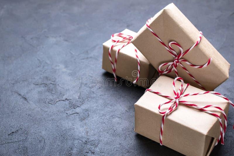 Donkere Kerstmisachtergrond Bruin die kraftpapier-document pakket met rood en wit koord op zwarte wordt gebonden stock afbeeldingen