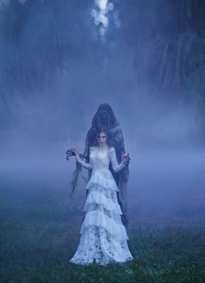 Donkere Koningin met keurig kapsel in een witte uitstekende kleding met een bloemenpatroon en een zilveren halsband die zich in e stock foto