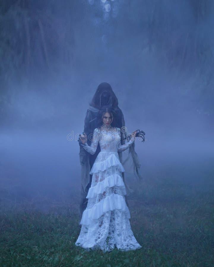 Donkere Koningin met keurig kapsel in een witte uitstekende kleding en een zilveren halsband, die zich in een boshoogtepunt van d stock foto