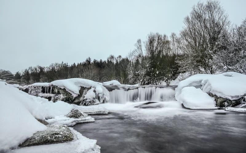 Donkere ochtend, rivier in de winter, maakt de lange blootstelling rond tot water melkachtig vlot, sneeuw en ijs stock foto