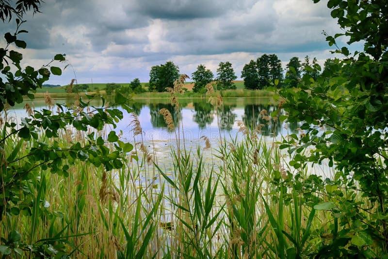 Donkere onweerswolken en bezinningen over de meerwaterspiegel stock fotografie