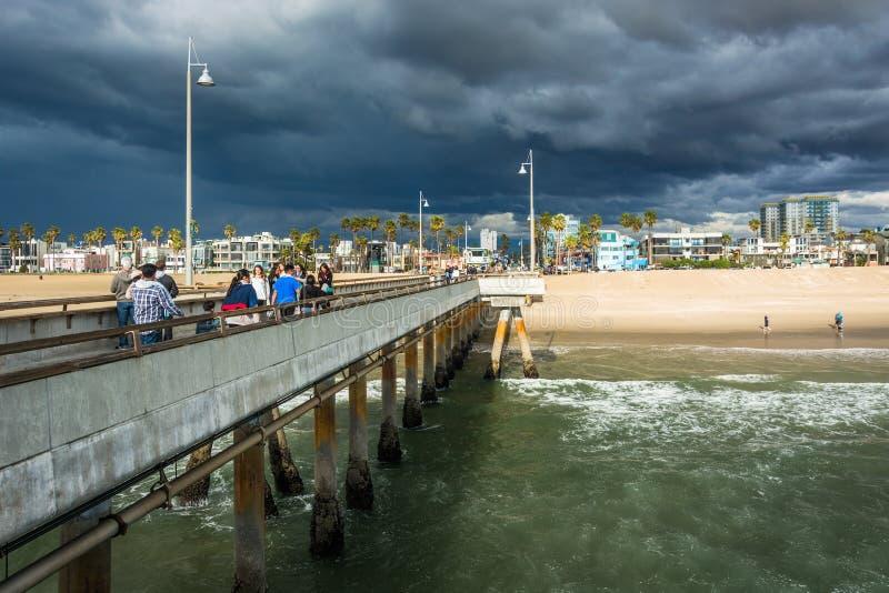 Donkere onweerswolken over de het visserijpijler en strand in Venetië stock fotografie