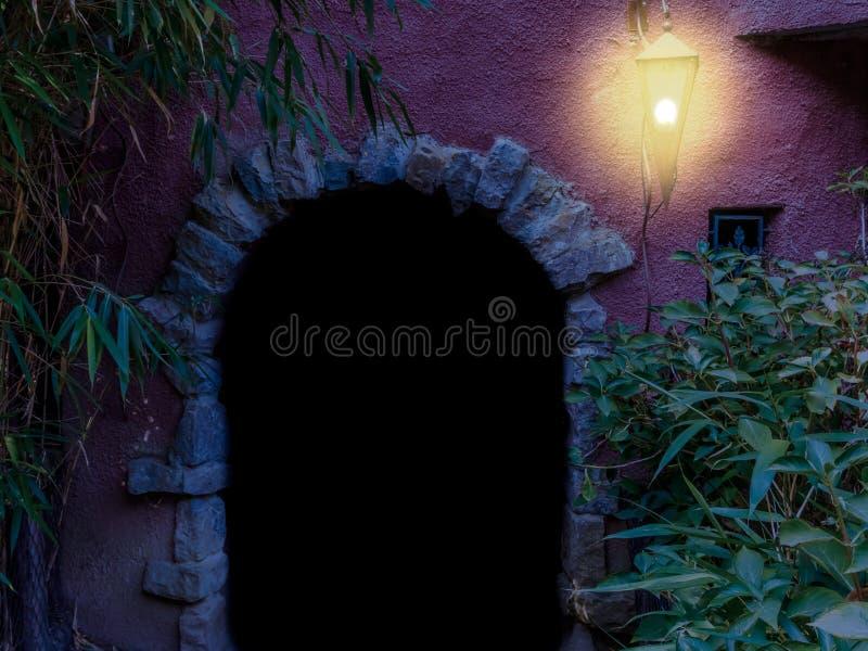 Donkere overspannen deuropening met een aangestoken lantaarn 's nachts, middeleeuwse architectuurachtergrond royalty-vrije stock afbeeldingen
