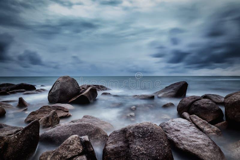 Donkere rotsen in een blauwe oceaan onder bewolkte hemel in een slecht weer , L stock foto