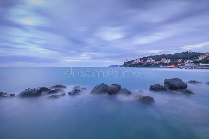 Donkere Rotsen in een blauwe oceaan op schemering. Castiglioncello, Italië stock afbeelding