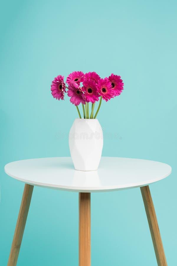 Donkere roze gerberas in een vaas op een retro lijst Gelukkige het Suikergoed Blauwe Gekleurde Achtergrond van de Moeder` s Dag stock afbeelding