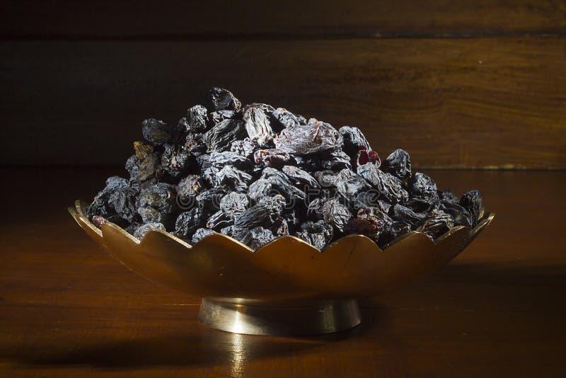 Donkere rozijnen in een metalen kom royalty-vrije stock foto