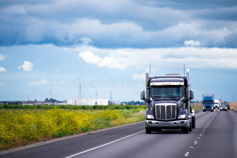 Donkere semi vrachtwagen met verkeer op weg in Californië royalty-vrije stock foto's