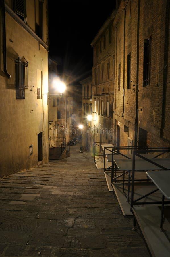 Donkere smalle steeg met oude gebouwen en straatlantaarns in Siena, Toscanië royalty-vrije stock afbeeldingen