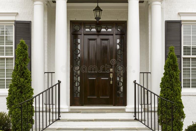 Donkere voordeur met witte kolommen stock fotografie