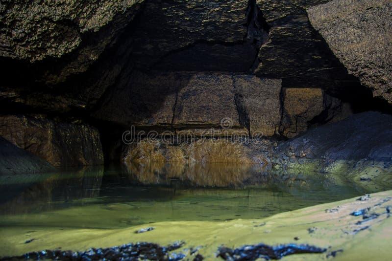 Donkere vuile overstroomde verlaten kalksteenmijn stock afbeelding
