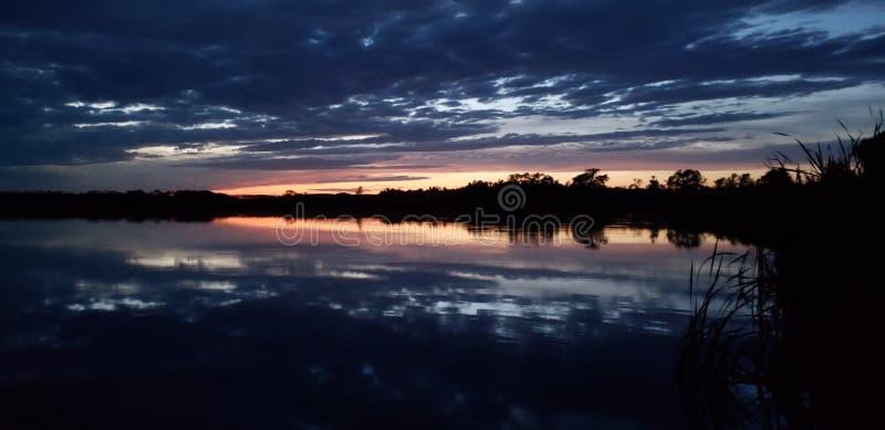 Donkere weerspiegelende zonsondergang op een prairiemeer stock foto's
