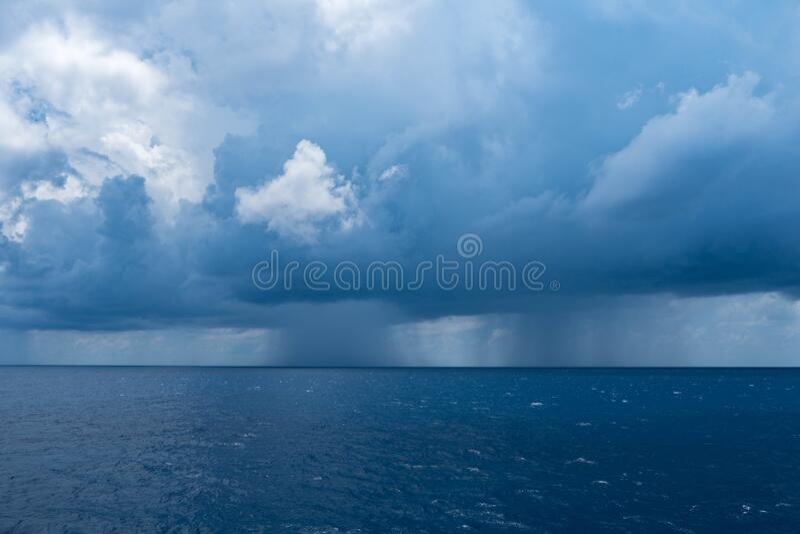 Donkere wolken aan de hemel bij het vallen van regen op zee stock foto