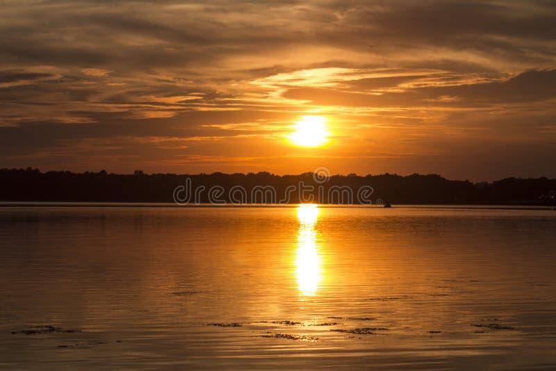 Donkere zonsondergang over het meer stock foto