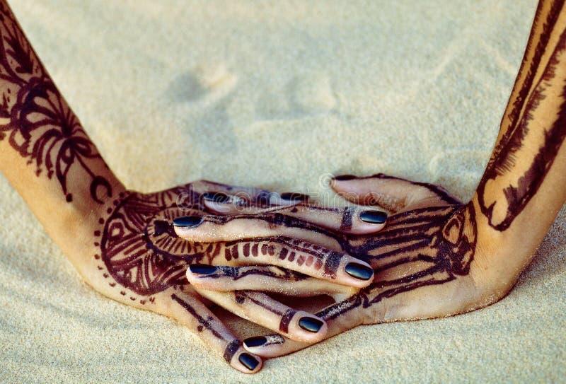 Donkere zwarte manicure op geschilderde mehndihanden op zand stock fotografie