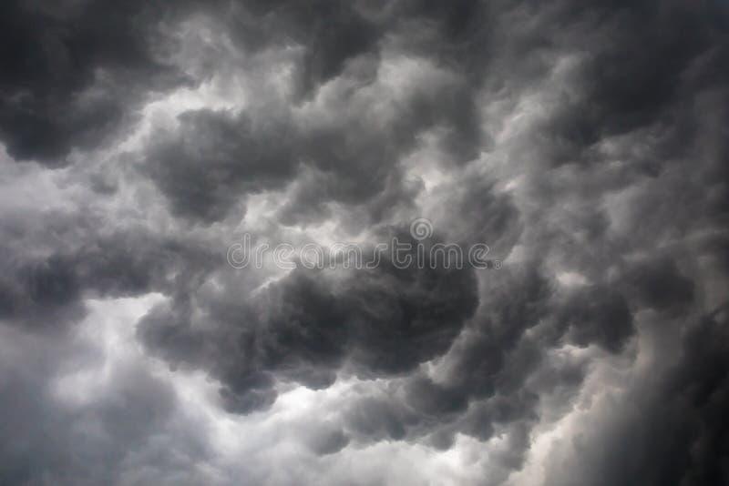 Donkere of zwarte wolken op de hemel vóór onweer het regenen stock foto
