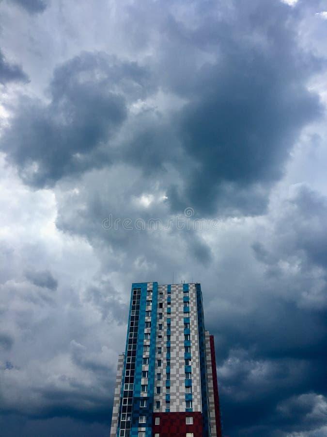 Donkergrijze Onweerswolken in de stad vóór de zware regen met een gebouw met meerdere verdiepingen stock afbeelding