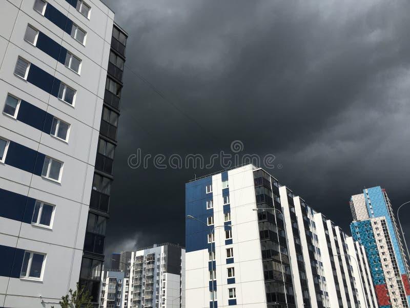 Donkergrijze Onweerswolken onder de bouw met meerdere verdiepingen vóór de zware regen stock fotografie