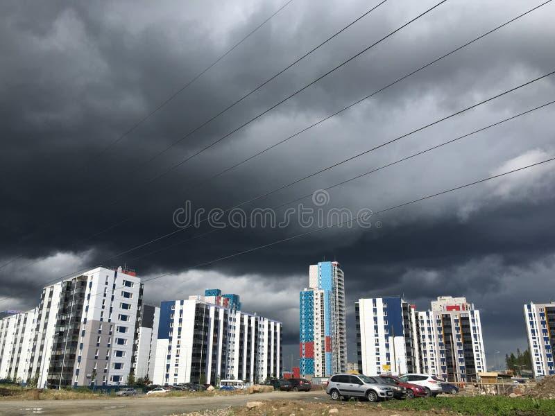 Donkergrijze Onweerswolken onder de bouw met meerdere verdiepingen vóór de zware regen royalty-vrije stock foto