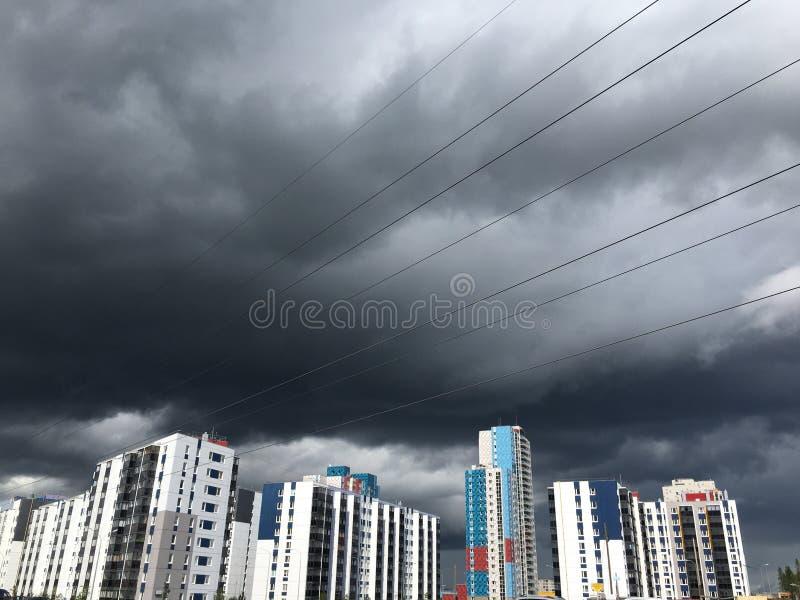 Donkergrijze Onweerswolken onder de bouw met meerdere verdiepingen vóór de zware regen royalty-vrije stock fotografie