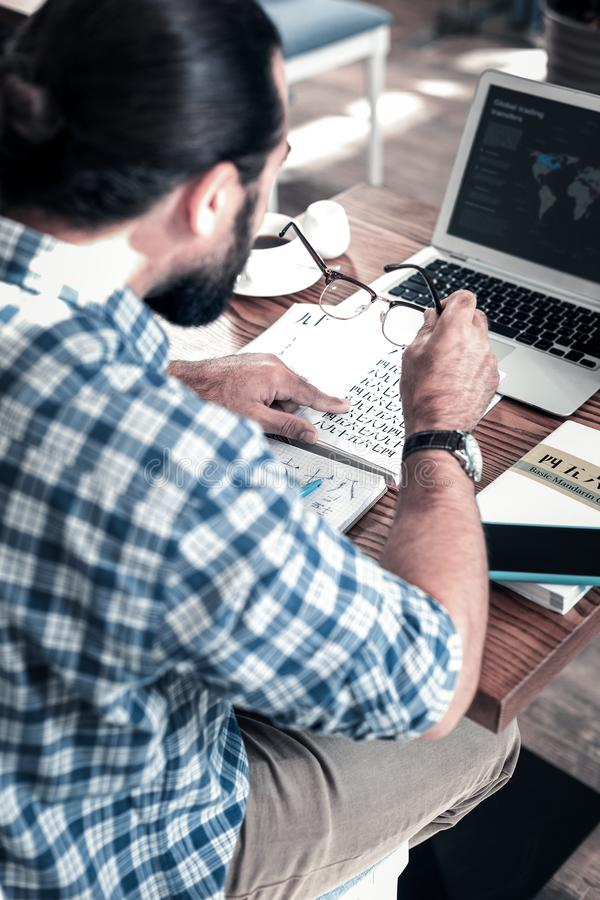 Donkerharigezitting voor zijn laptop terwijl het bestuderen van Chinees royalty-vrije stock foto