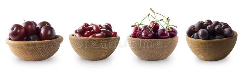 Donkerrode bessen op een witte achtergrond Cornels, pruimen, kersen en druiven in een houten kom stock afbeeldingen