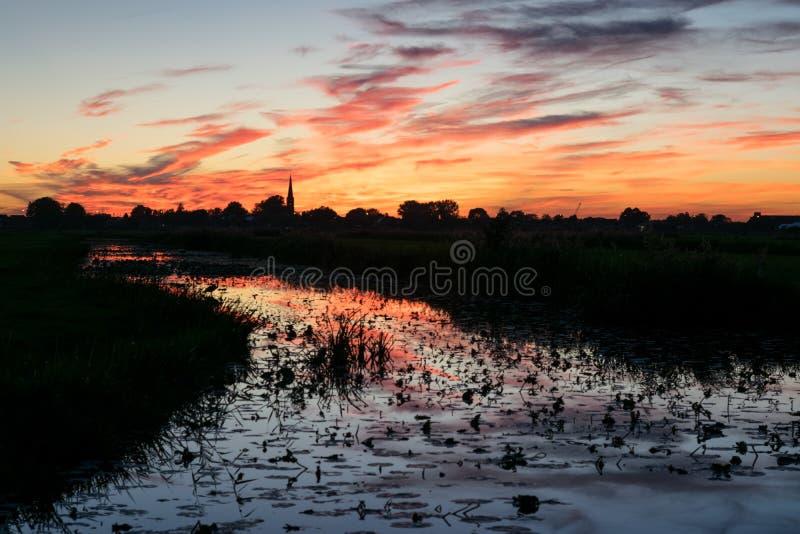Donkerrode en oranje hemel met bezinningen in het water van een kanaal dichtbij Gouda, Nederland royalty-vrije stock foto's