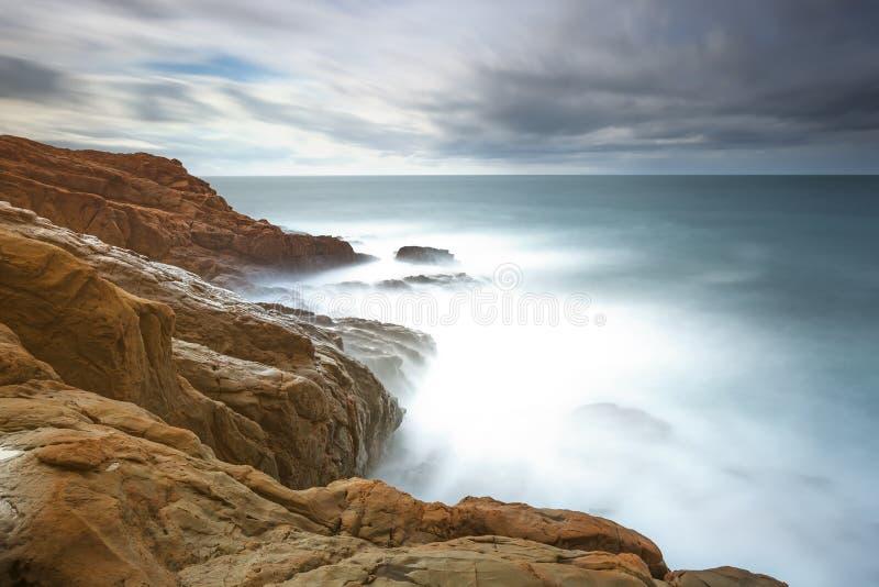 Donkerrode rotsen, schuim en golven, overzees onder slecht weer. stock fotografie