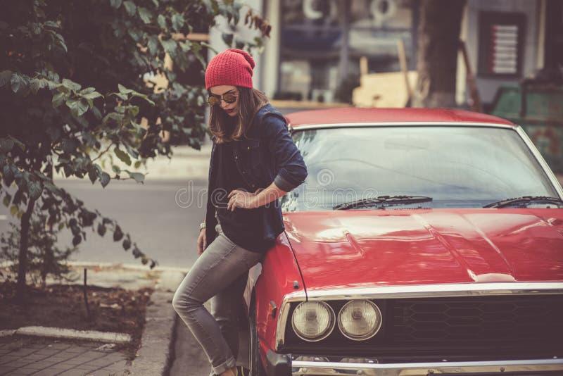 Donna abbastanza alla moda che fa una pausa la retro automobile fotografia stock