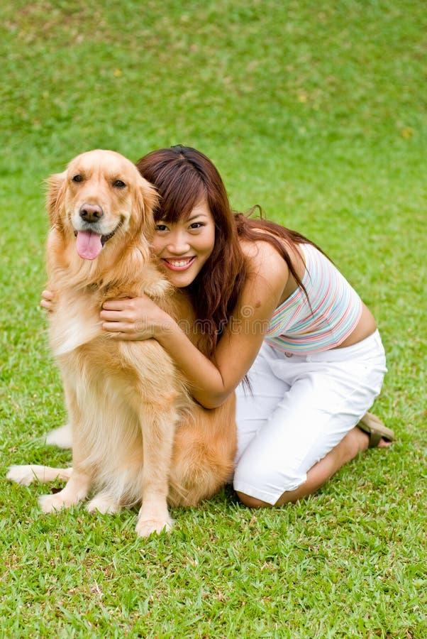Donna abbastanza asiatica con il cane fotografia stock