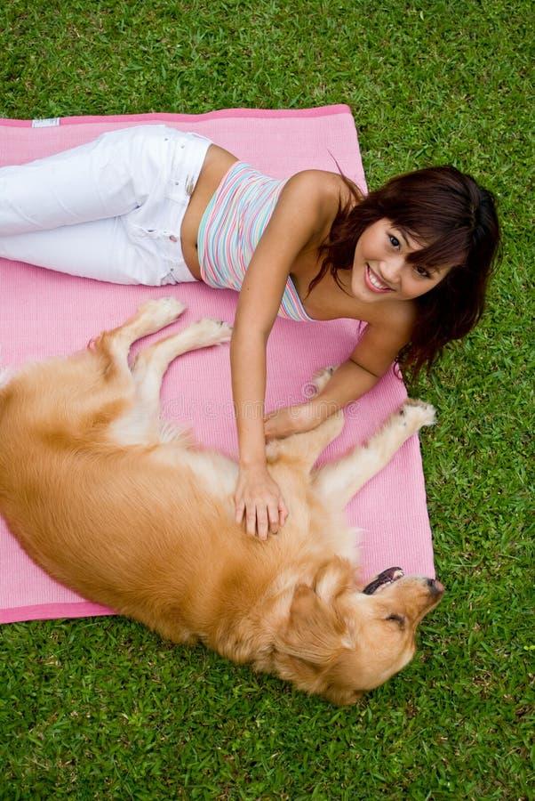Donna abbastanza asiatica con il cane immagine stock