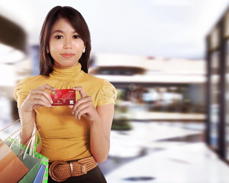 Donna abbastanza asiatica con il sacchetto della spesa che mostra la carta di credito fotografie stock libere da diritti