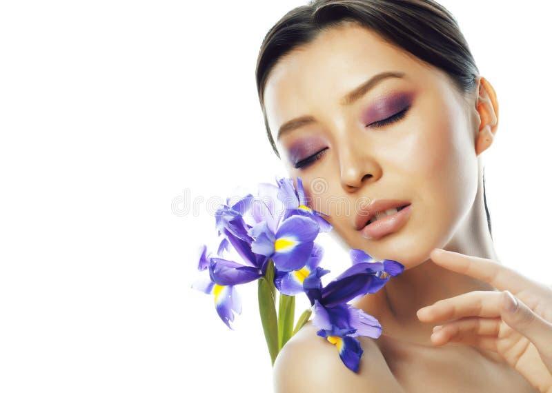 Donna abbastanza asiatica dei giovani con la fine porpora dell'orchidea del fiore sull'isolante fotografie stock libere da diritti