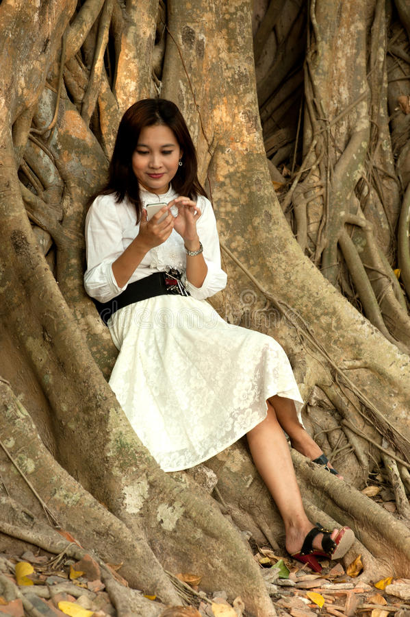 Donna abbastanza asiatica sul telefono al vecchio albero della radice. fotografia stock