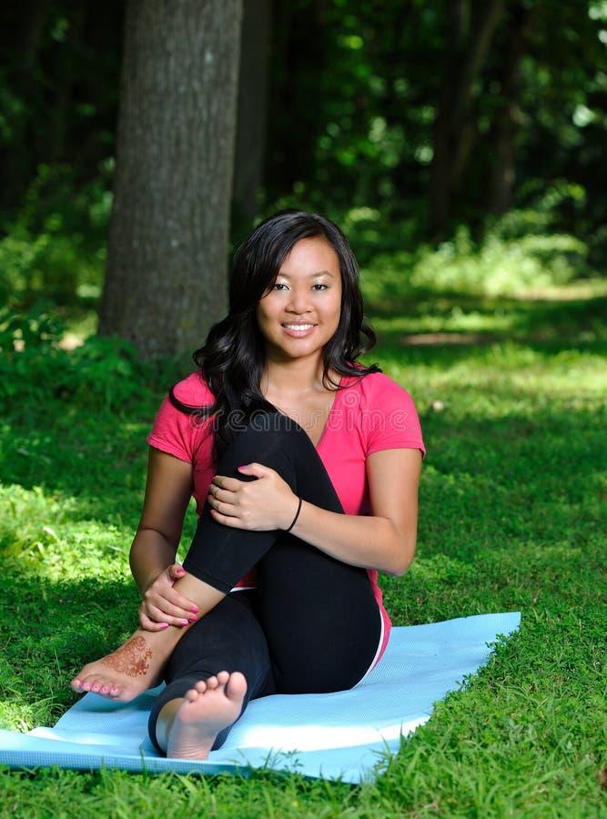 Donna abbastanza asiatica - yoga nella sosta fotografie stock