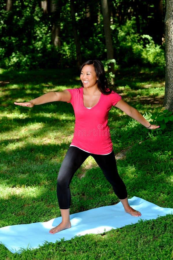 Donna abbastanza asiatica - yoga nella sosta immagine stock