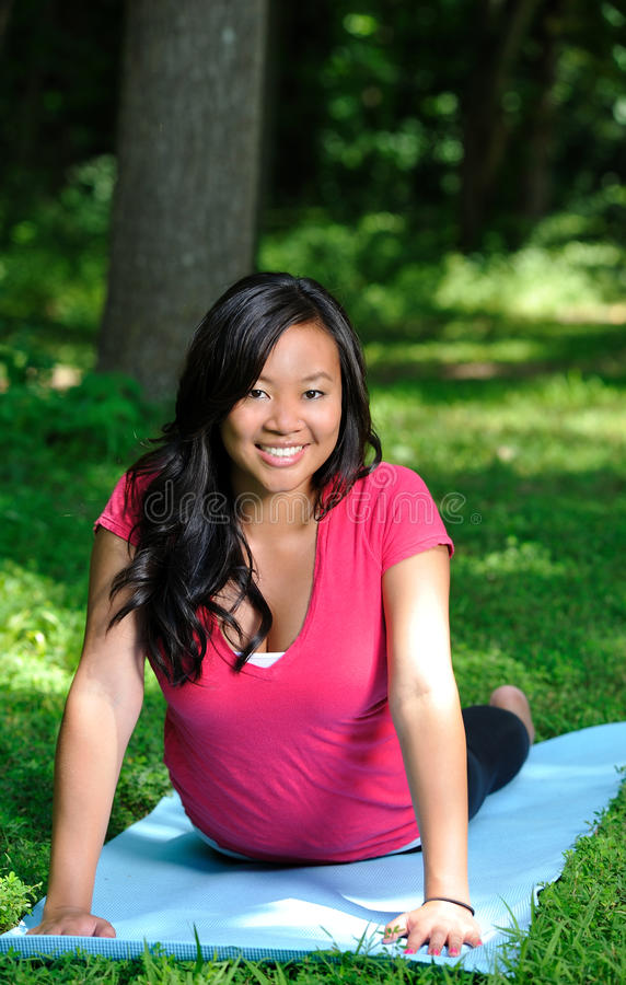 Donna abbastanza asiatica - yoga nella sosta immagine stock libera da diritti