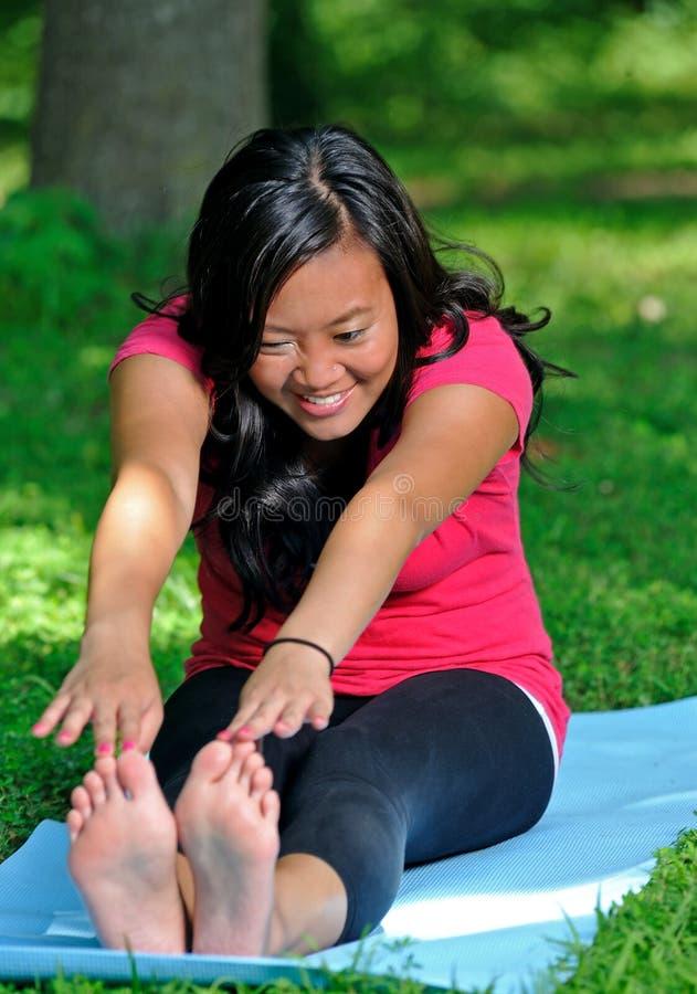 Donna abbastanza asiatica - yoga nella sosta fotografia stock