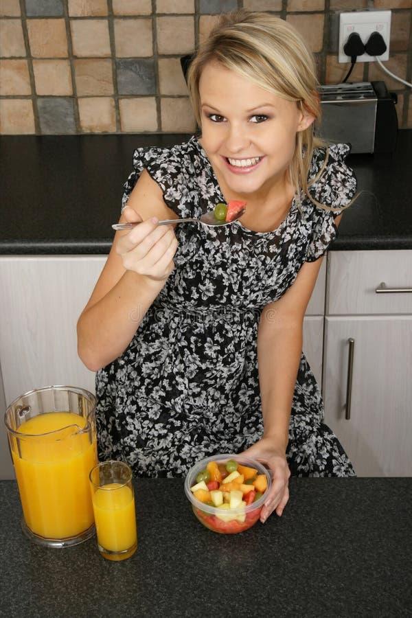 Donna abbastanza bionda che mangia prima colazione fotografia stock