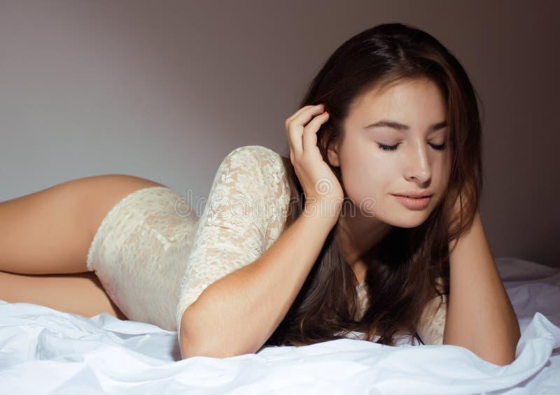 Donna abbastanza castana che si situa a letto biancheria sensuale concetto della gente di - Letto che si chiude ...