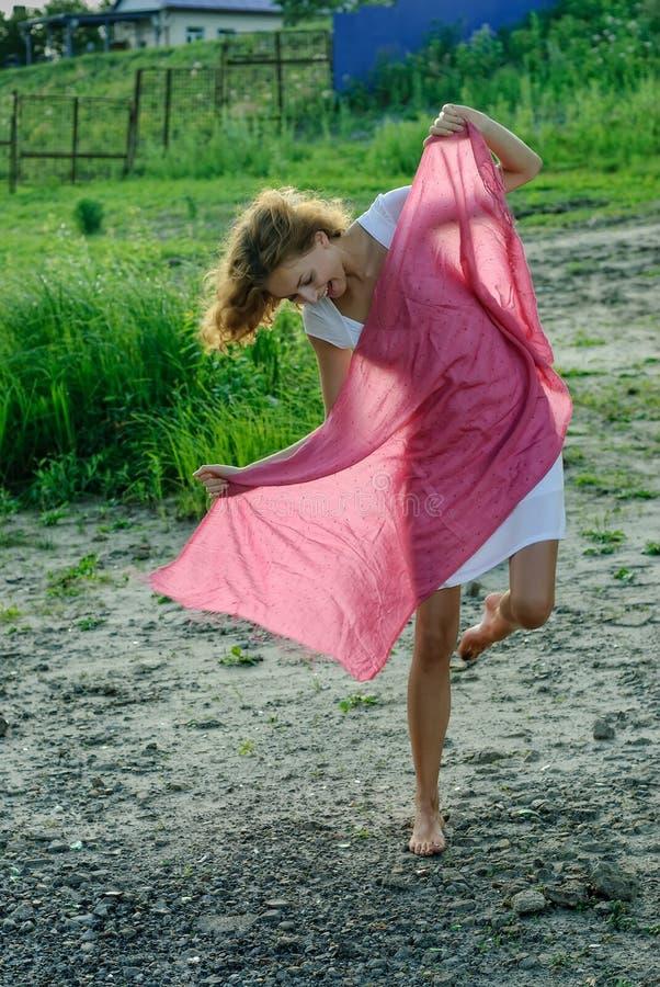 Donna abbastanza divertente dei giovani con la sciarpa rossa fotografia stock