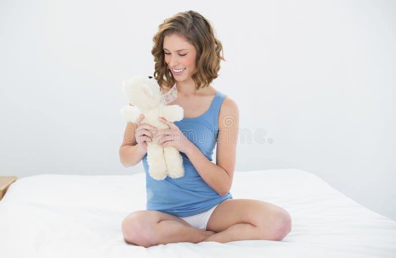 Donna abbastanza dolce che tiene il suo orsacchiotto bianco che lo esamina che si siede sul suo letto fotografia stock libera da diritti